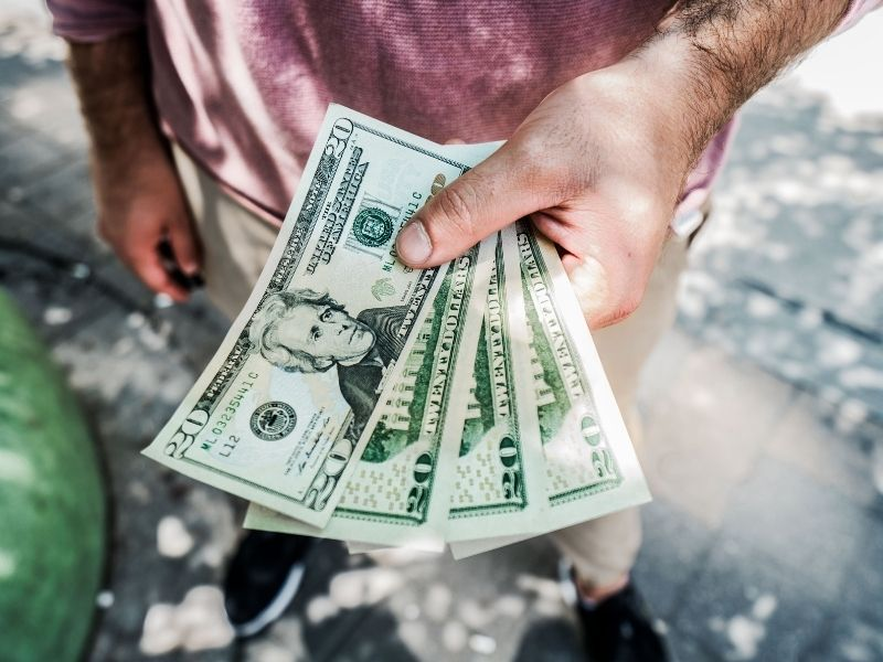 man holding spread out 20 dollar bills in his hand