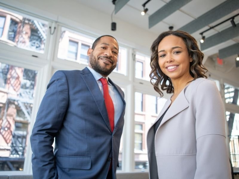 a man and a woman in business suits smiling at the camera